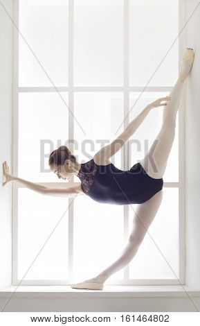 Classical Ballet dancer portrait. Beautiful graceful ballerine in black practice standing split ballet position at window background. Ballet class training, high-key. Vertical image