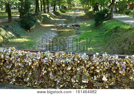 Padlocks On Bridge Of Love And Rivulet