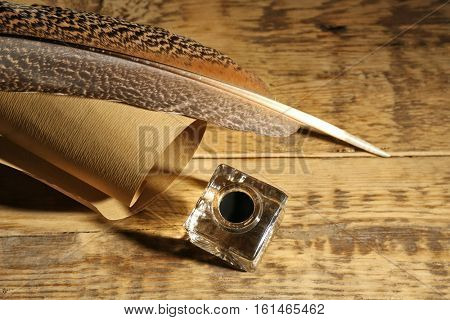 Feather pen with inkwell and scroll on wooden background