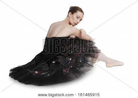 Tired ballerina sits relax after perfomance against white background, isolated. Professional dancer in black swan dress. Choreography concept