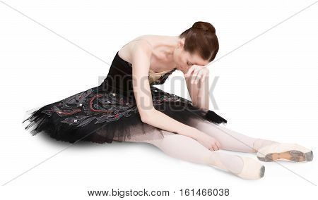 Tired ballerina sits relax after perfomance against white background, isolated. Professional dancer in black swan dress. Choreography hardworking concept