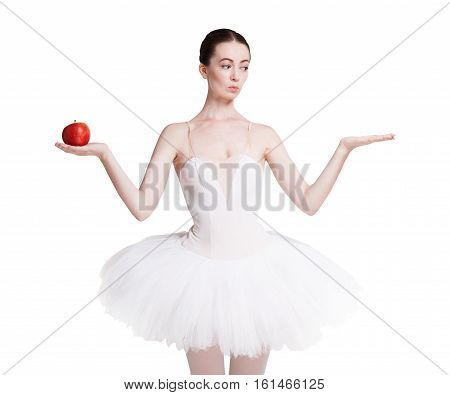 Graceful ballet dancer shows apple and something in another, empty hand, isolated on white. Slimming and weight loss concept, copy space