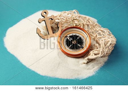 Wooden anchor and compass in sand on blue background. Columbus Day concept