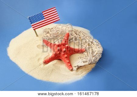 USA flag, starfish and net in sand on blue background. Columbus Day concept