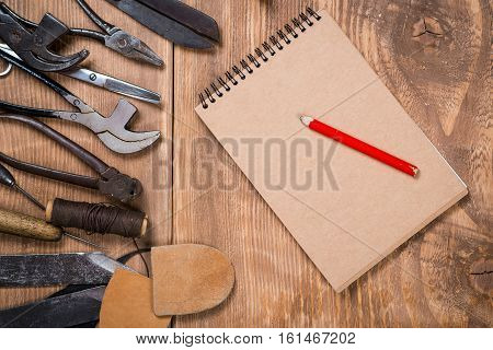 Set of tools, notebook, pencil for shoemaker on the wooden background.
