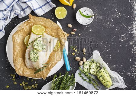 Fresh cod before baking with homemade green butter with herbs on a dark background with slices of lemon, thyme, sea salt. Top view. Healthy food concept