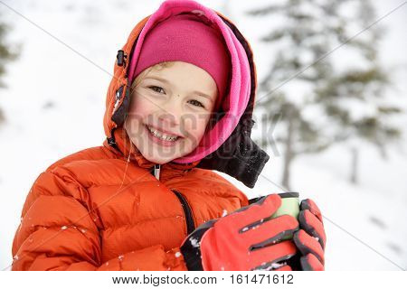 Beautiful girl enjoying winter and snow dressed in warm clothes drinking warm thermos tea. Active family lifestyle outdoor and natural childhood carefree childhood concept.
