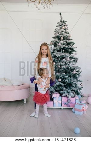 big sister hugging little sister near a Christmas tree and gift boxes