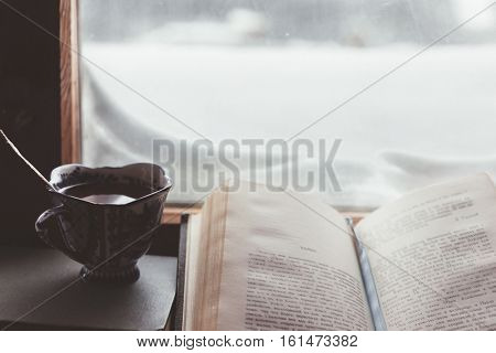 Warm and comfy winter concept. Book, cup of tea and candlestick on wooden window sill in old house. Reading and relaxing in cold snowy weather at home. Quiet silent homely scene.