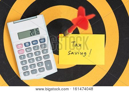 Tax saving note with dart arrow on bullseye and calculator over dartboard
