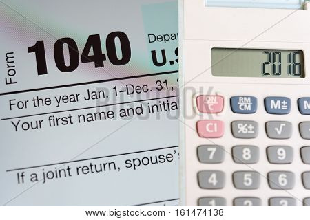 Tax form 1040 on tablet screen and calculator