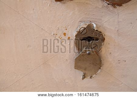 Keyhole with cap on the painted metallic door. Close up view.
