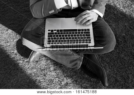 High angle low section of businessman using laptop while sitting on turf