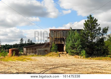 Old abandoned defaulted industrial building which stands with rusty and empty silo