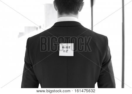 Rear view of young businessman with hire me sticky note at office