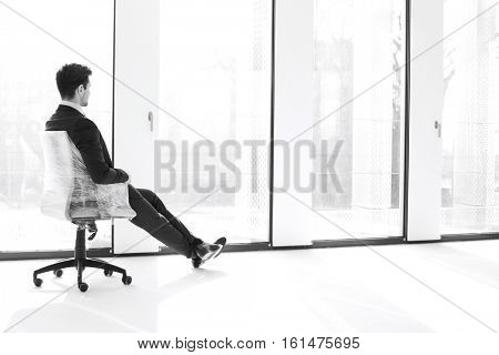 Full length side view of thoughtful young businessman sitting on chair by windows in new office