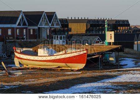 Red fishing boat pulled up on the land and is docked in the beach in the small fishing village