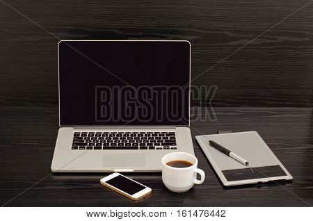 Open notebook graphics tablet coffee cup and phone on a black table
