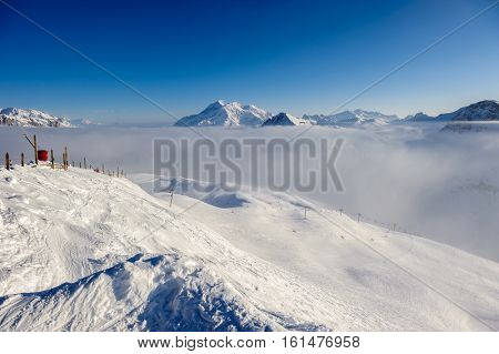 Alpine winter mountain landscape with low clouds. French Alps covered with snow in sunny day. Val-d'Isere, France
