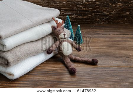 Stack of knitted clothes in nude beige tones. Cashmere sweaters wool cardigan felt elk and little Christmas tree on a wooden background. Concept of Winter time and Christmas holiday. Copy space.