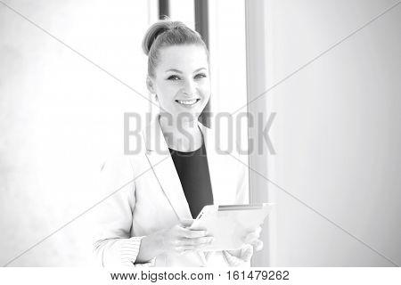 Portrait of smiling young businesswoman holding digital tablet in office