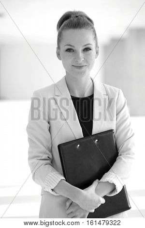 Portrait of confident young businesswoman holding file in office