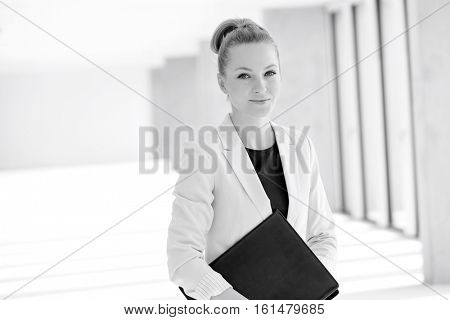 Portrait of confident young businesswoman with file in new office
