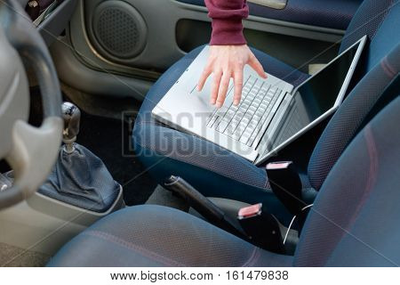 Hooded Thief Stealing A Computer Laptop From A Parked Car