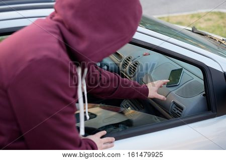 Hooded Thief Stealing A Mobile Phone From A Parked Car