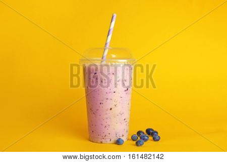 Delicious berry milkshake in plastic cup on yellow background