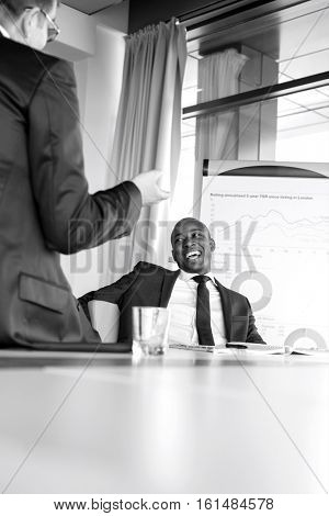 Cheerful young businessman talking with male colleague in board room