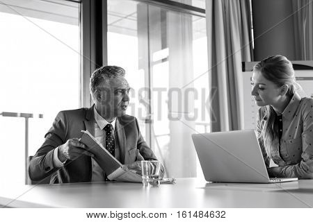 Mature businessman showing documents to female colleague at conference table