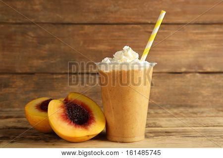 Tasty peach milkshake with cream in plastic cup on wooden background