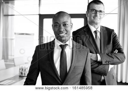 Portrait of confident businessman with male colleague in office