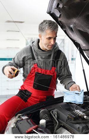 Mechanic checks the engine oil level dipstick