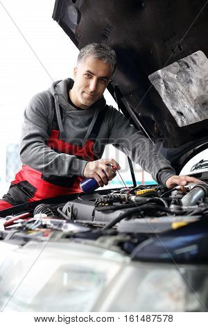 Car mechanic cleans and lubricates the screws under the hood of the car poster
