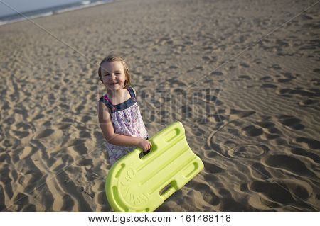 Girl with green swimming board smiling, sicily