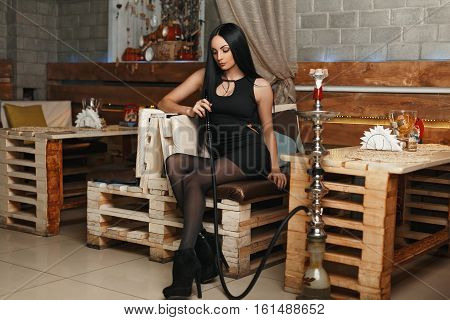 Beautiful Young Woman In Stylish Black Clothes Sitting On A Sofa And Smokes A Hookah.