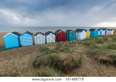 A close up view of a line of colourful beach huts at Southwold Suffolk