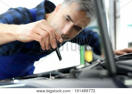 Steering fluid change. The mechanic fills the tank power steering fluid. Mechanic tightened the valve steering fluid reservoir. Car mechanic exchanges steering system fluid. poster