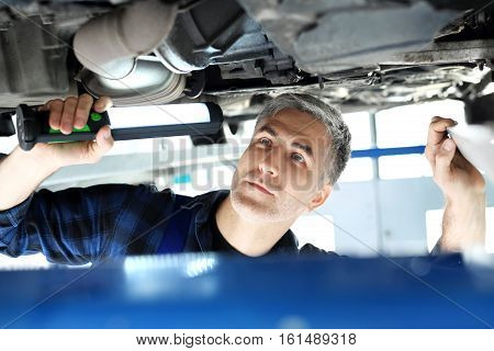 Car repair shop, mechanic repairing a car. The car in the garage, the mechanic checks the status of the chassis.
