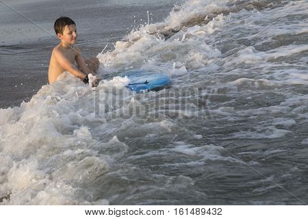 Boy sitting ang splashing through the waves on the seashore