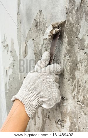 hand in gloves scraping off old wet wallpaper with spatula