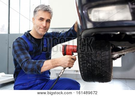 Tire service. Replacing the tires on the car. Car mechanic tightened wrench pneumatic wheels in the car.