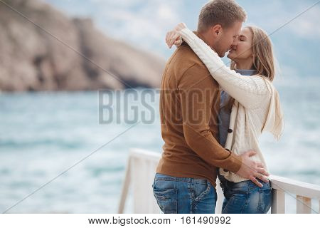 Young couple blond guy with short hair in a brown sweater and blue jeans and a blonde girl with straight long hair,dressed in a white jacket and gray turtleneck,spend time together,standing arm in arm on a white wooden pier near the sea in autumn