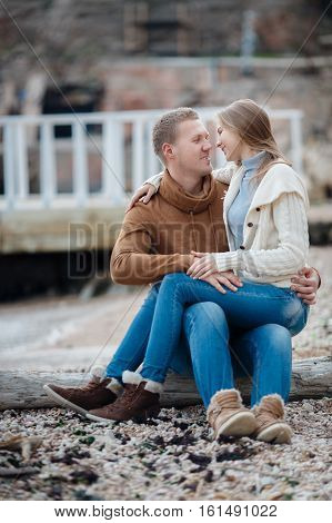 Young couple blond guy with short hair in a brown sweater and blue jeans and a blonde girl with straight long hair,dressed in a white jacket and gray turtleneck,spend time together,sitting arm in arm on the shore near sea in autumn