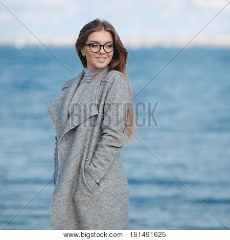 Stylish young woman model looks with long blond hair,wears black-rimmed glasses,slim figure,light makeup,dressed in a grey turtleneck and a grey coat posing on the street alone on a deserted beach on a blue sea background