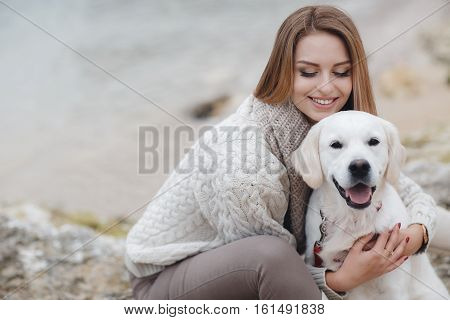 Beautiful young woman with long straight hair, light red,dressed in a white knitted sweater with a big beige collar,light make-up and large black eyelashes,spending time sitting on the beach with a friend,pet,dog,breed Golden Retriever