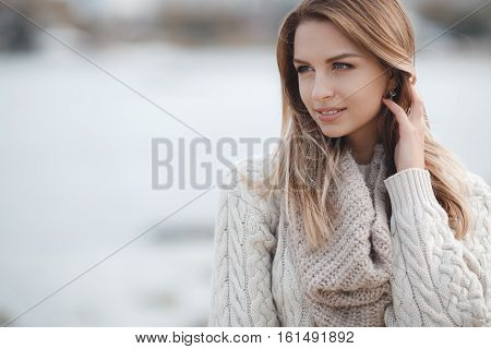 Spring portrait beautiful woman with blond, long,straight hair and grey eyes,large black eyelashes,light makeup,pink lipstick,wearing jewelry,wearing a knitted sweater is white with a large beige collar,posing outdoors in early spring.
