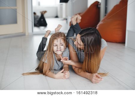 Beautiful mother,lying on white wooden floor with his little daughter in the gym in front of the mirror,both dressed in light gray shirts and gray jeans,barefoot,both have long straight brown hair color,a mother talks with her daughter